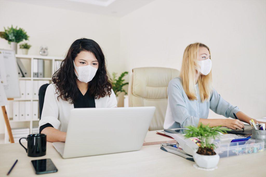 lavoratrici con mascherine per virus durante coronavirus