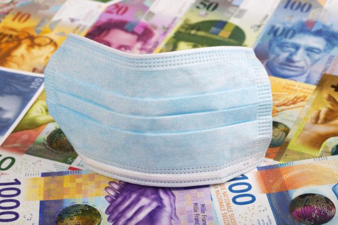 mascherina sopra soldi dell'impatto economico del coronavirus