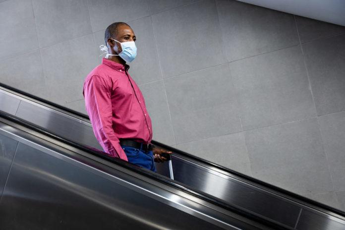uomo sulle scale mobili con mascherina per coronavirus