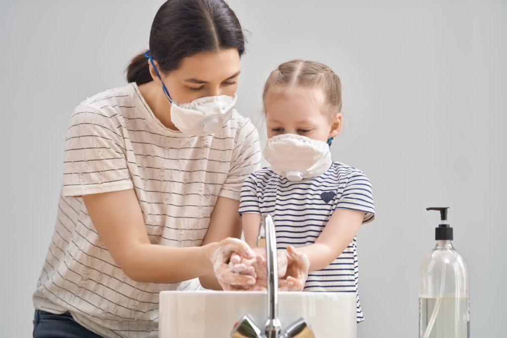 mamma e figlia con mascherine lavano le mani